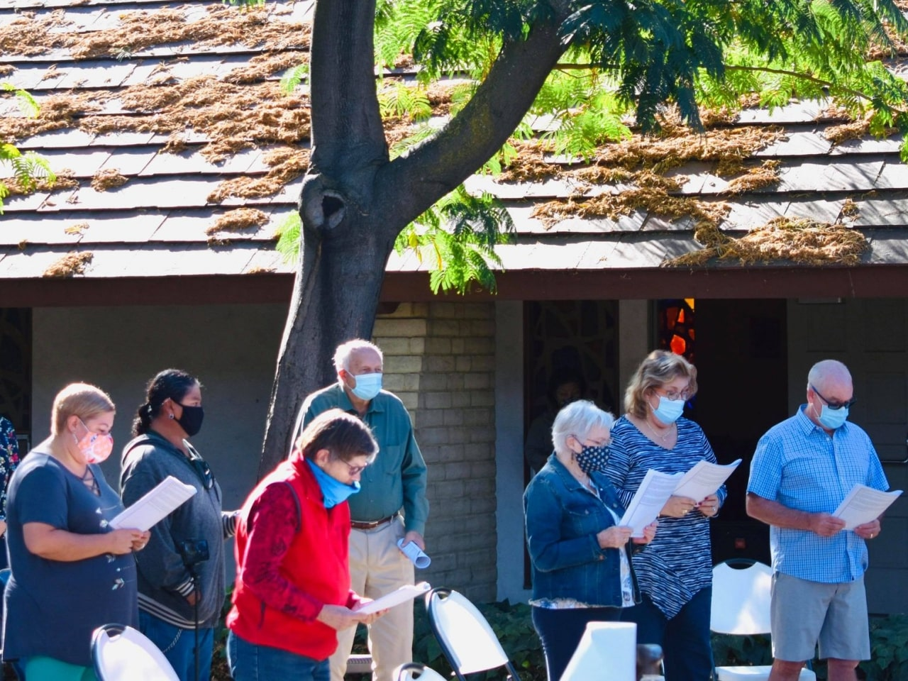 Group of standing people wearing face masks during outdoor church service in San Jose, CA