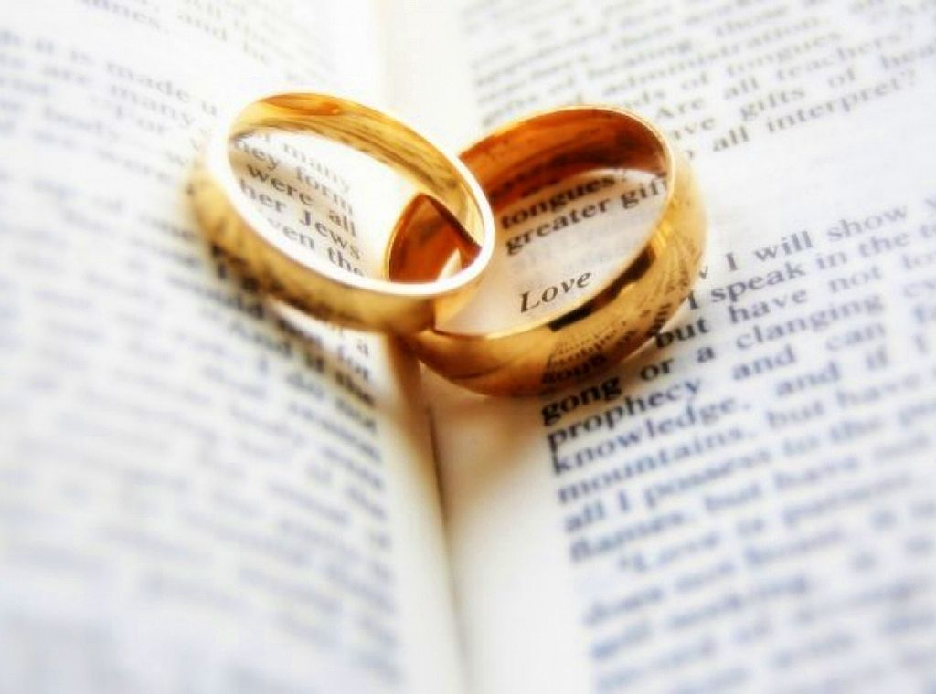 Two gold rings laying in the fold of an open Bible
