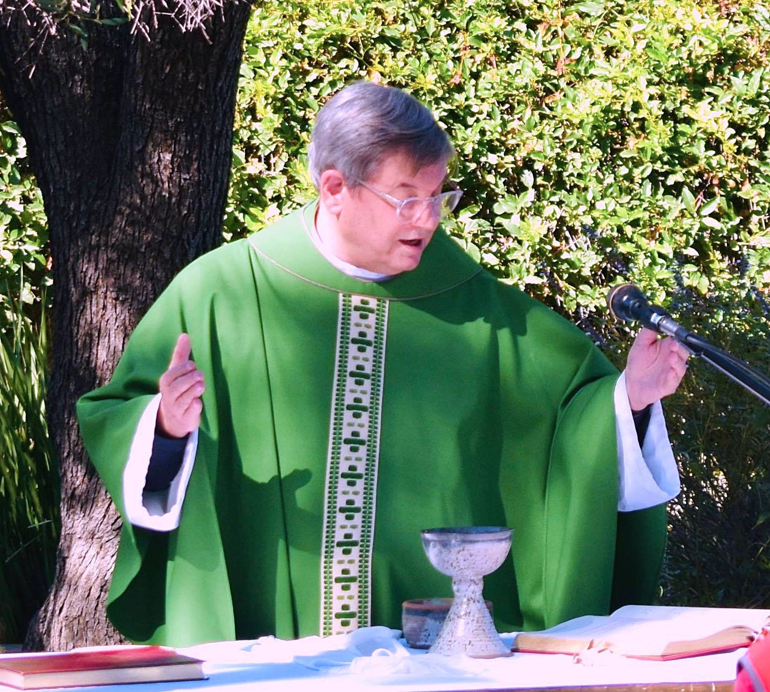 Priest standing outside officiating Sunday church service